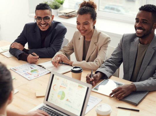 photo-of-three-people-smiling-while-having-a-meeting